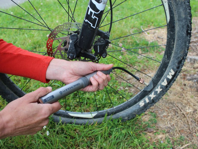 Mini bike pump pumping up a tyre. goRide